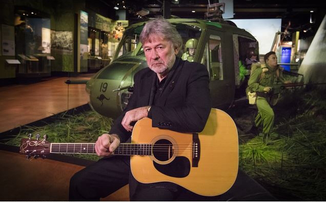 Singer-songwriter John Schumann with his guitar alongside a Vietnam War exhibit in the Australian War Memorial.