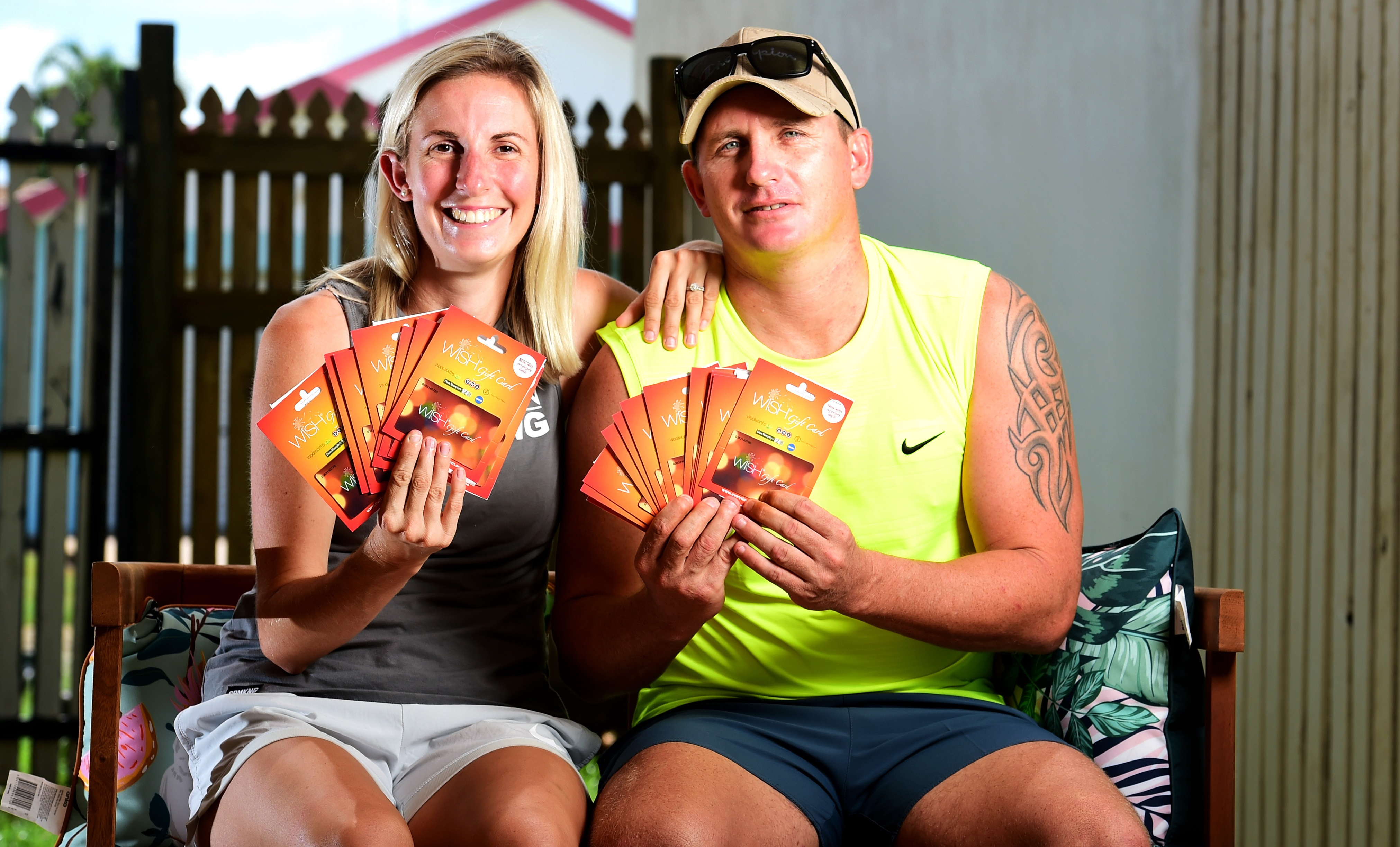 Beau King and Stacey Lyon, sitting down in casual, light clothing. Both are holding fistfuls of supermarket gift cards.
